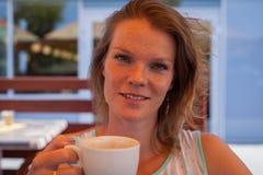 La giovane donna su un terrazzo del caffè di estate gode di un caffè Fotografie Stock Libere da Diritti