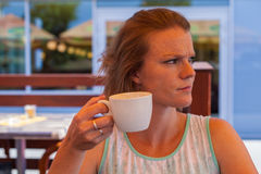 La giovane donna su un terrazzo del caffè di estate gode di un caffè immagini stock libere da diritti