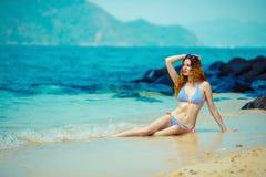 La giovane donna su una spiaggia in bikini Immagine Stock