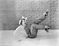 La giovane donna sul sembrare al suolo sorpresa dopo avere scoperto che il pattinaggio a rotelle è un oggetto sdrucciolevole (tut Immagine Stock