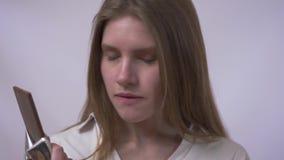 La giovane donna sulla dieta, tiene il cioccolato, lo odora, ma non mangia stock footage