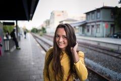 La giovane donna sveglia in vestito luminoso sta sulla stazione ferroviaria fotografia stock libera da diritti