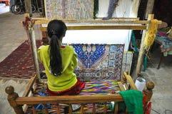 La giovane donna tesse un tappeto sul telaio a mano Fotografia Stock Libera da Diritti