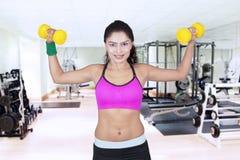 La giovane donna tiene le teste di legno nel centro di forma fisica Fotografia Stock