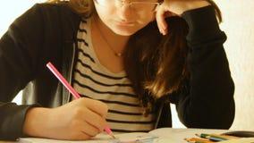 La giovane donna tiene una matita e disegna a casa Coloritura per gli adulti ed i bambini Per distensione della tensione Libro da stock footage