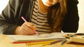 La giovane donna tiene una matita e disegna a casa Coloritura per gli adulti ed i bambini Per distensione della tensione Libro da archivi video
