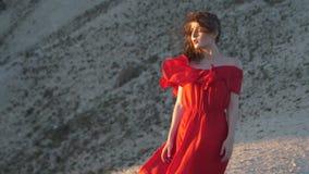 La giovane donna in tunica rossa esamina il vento di salto del sole video d archivio