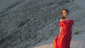 La giovane donna in tunica rossa esamina il vento di salto del sole stock footage