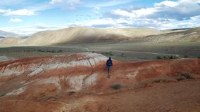 La giovane donna turistica con lo zaino ed il cappello scala la montagna di pietra rossa C'è paesaggio scenico e nuvoloso irreali archivi video