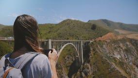 La giovane donna turistica di vista posteriore con lo zaino prende la foto dello smartphone del paesaggio epico al Big Sur iconic video d archivio