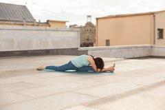 La giovane donna in un allungamento di yoga e la curvatura posano Immagini Stock Libere da Diritti