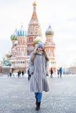 La giovane donna in un blu ha tricottato il cappello ed il cappotto di visone grigio fotografie stock