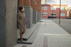 La giovane donna in un cappotto beige sta vicino ad un muro di mattoni fotografia stock