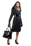 La giovane donna in un cappotto nero con un sacchetto fotografie stock libere da diritti