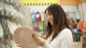 La giovane donna in un deposito di prodotti per la casa sceglie i piatti stock footage