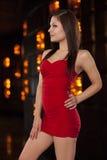 La giovane donna in un poco vestito rosso posa con confidenza davanti a Fotografia Stock Libera da Diritti