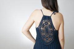 La giovane donna in un vestito ha tricottato su un fondo grigio immagine stock