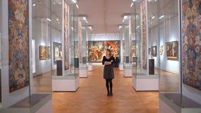 La giovane donna in un vestito nero visitting il museo ed esamina le mostre stock footage