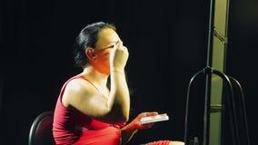 La giovane donna in un vestito rosso davanti ad uno specchio con una spazzola mette l'ombra sulle palpebre video d archivio