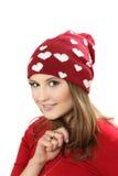 La giovane donna in un vestito rosso ed in uno spiritello malevolo con i cuori Fotografie Stock Libere da Diritti