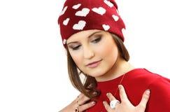 La giovane donna in un vestito rosso ed in uno spiritello malevolo con i cuori Fotografia Stock