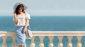 La giovane donna in una blusa bianca, corregge la gonna ed il cappello sull'sedere Fotografia Stock