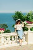 La giovane donna in una blusa bianca, corregge la gonna ed il cappello sull'sedere Immagini Stock Libere da Diritti