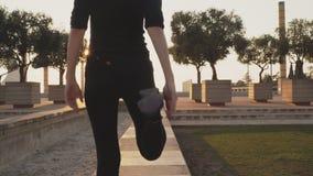 La giovane donna in una tuta sportiva nera allunga i muscoli della gamba prima di pareggiare gi? la via in tempo caldo soleggiato
