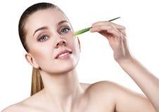 La giovane donna usa l'olio di vera dell'aloe per pelle Fotografia Stock