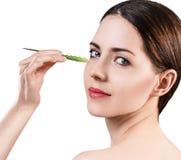 La giovane donna usa l'olio di vera dell'aloe per pelle Immagini Stock