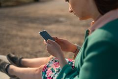La giovane donna utilizza il telefono in un parco del palazzo che si siede su una fontana - chiuda su fotografie stock