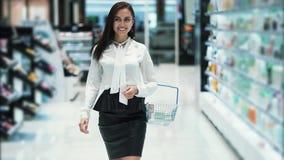 La giovane donna va al deposito dei cosmetici con il canestro, movimento lento, steadicam sparato