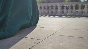La giovane donna in vestito lungo che cammina lungo il percorso di pietra, si allontana, primo piano i piedi, rallentatore stock footage