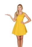 La giovane donna in vestito sorride e mostra il pollice. Fotografia Stock