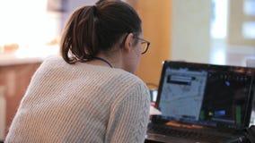 La giovane donna in vetri ed in un'acconciatura della coda di cavallo lavora dietro il computer portatile nero video d archivio