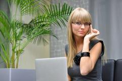 La giovane donna in vetri lavora con un computer portatile Fotografia Stock Libera da Diritti