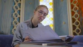 La giovane donna in vetri sta lanciando attraverso il menu in un ristorante asiatico archivi video