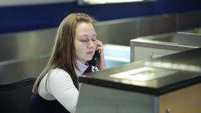 La giovane e bella donna sta sedendosi nell'area reception dell'aeroporto che chiama il telefono stock footage