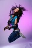La giovane e bella ragazza salta con la chitarra immagine stock