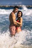 La giovane e coppia attraente sta divertendosi in acqua sulla spiaggia Immagini Stock