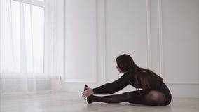 La giovane e donna graziosa che allunga la gamba muscles sul pavimento nello studio archivi video