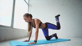 La giovane e ragazza atletica fa le gambe attive con le gambe per rinforzare le natiche archivi video