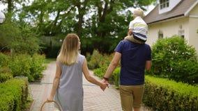 La giovane famiglia è otdoors di camminata al giorno Territorio dei cottage Canestro di picnic della tenuta della madre sulla sua video d archivio