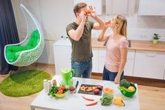 La giovane famiglia amorosa si diverte con i pomodori ed il peperoncino organici mentre cucina le verdure in cucina bianca vegeta fotografia stock