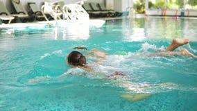 La giovane famiglia in buona salute insieme al loro bambino sta tuffando sotto l'acqua nel tenersi per mano della piscina Madre e stock footage