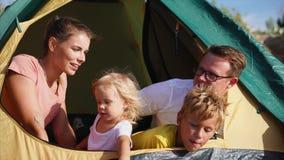La giovane famiglia che si siede in una tenda che guarda la distanza alla gente della natura è felice video d archivio