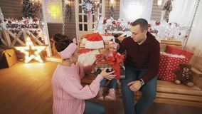 La giovane famiglia dà il regalo alla figlia all'oscillazione di natale Famiglia che si siede sull'oscillazione stock footage