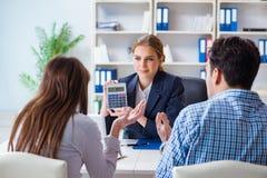 La giovane famiglia deludente all'alto tasso di interesse ipotecario di interesse in banca fotografie stock