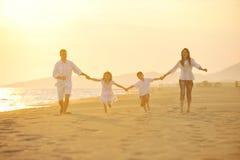 La giovane famiglia felice ha divertimento sulla spiaggia al tramonto Fotografia Stock Libera da Diritti