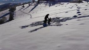 La giovane famiglia felice sta divertendo il gioco nella neve Allegro cadono nella neve La famiglia è insieme felice video d archivio